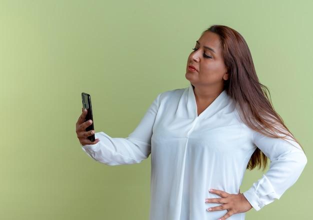 Toevallige kaukasische vrouw die van middelbare leeftijd en telefoon houdt en hand op heup zet