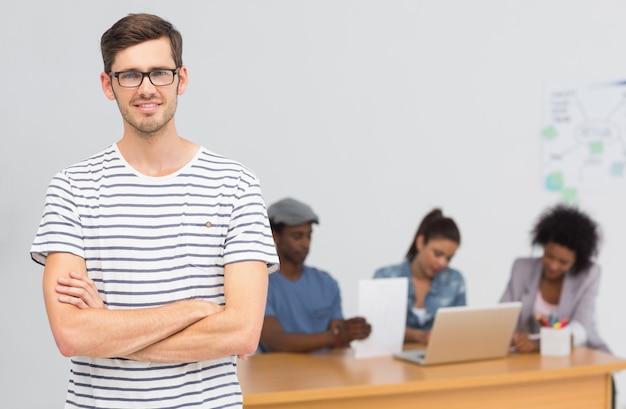 Toevallige mannelijke kunstenaar met collega's op achtergrond op kantoor