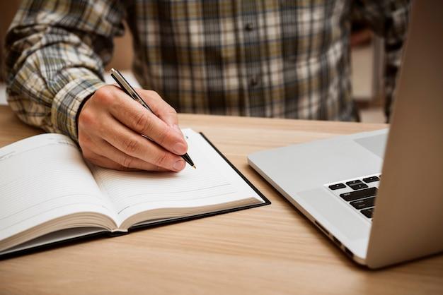 Toevallige mens die in leeg notitieboekje schrijft