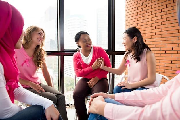 Toevallige multiethinic vrouwen die in cirkel in de vergadering zitten