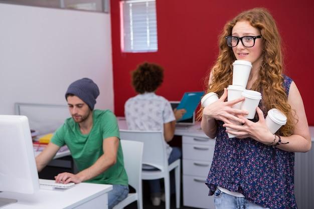Toevallige onderneemster die disposables glazen in bureau dragen