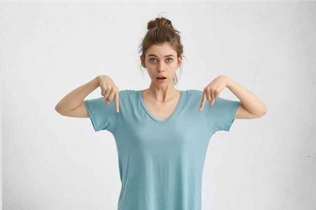 Toevallige verraste vrouw die haar vingers naar beneden richt