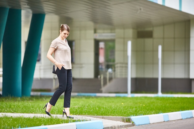 Toevallige vrij jonge vrouw die onderaan de stedelijke dag van de straatzomer loopt. zwarte jeans, schoenen met hoge hakken