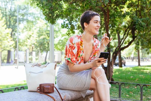 Toevallige vrouw die technologie in het park gebruiken
