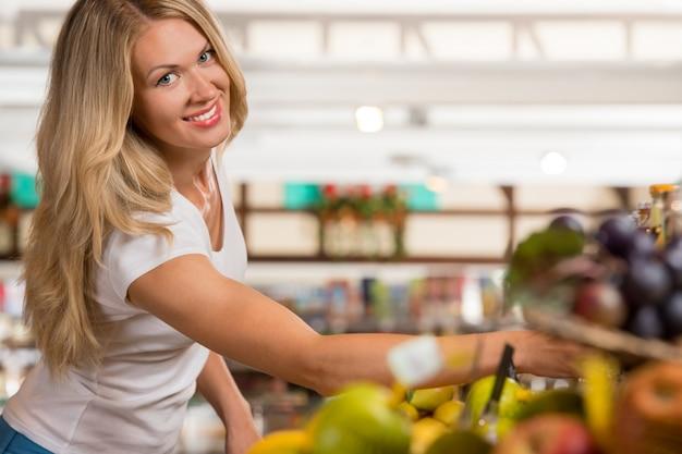 Toevallige vrouwenkruidenierswinkel die bij natuurvoedingsectie winkelen