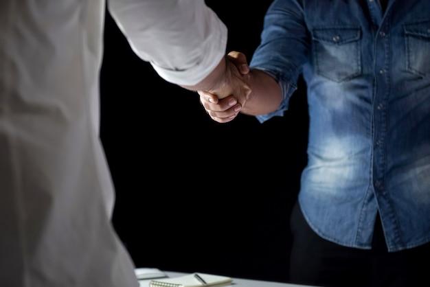 Toevallige zakenlieden die handdruk maken tijdens de vergadering bij nacht