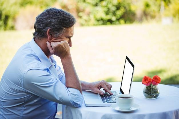 Toevallige zakenman gebruikend laptop en hebbend koffie