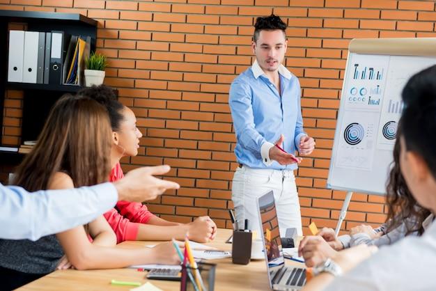 Toevallige zakenmanleider die de presentatie van de bedrijfverkoop in de vergadering leidt