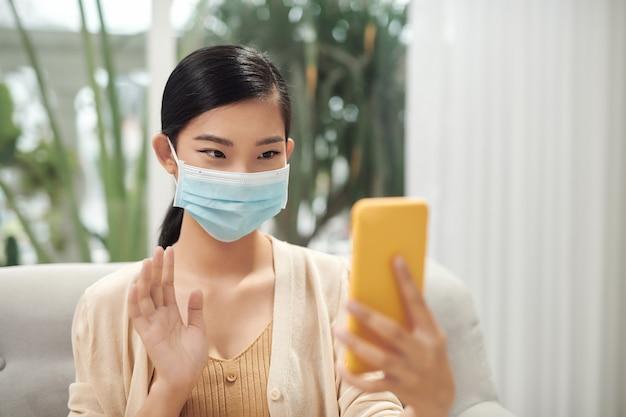 Toevallige ziektevrouw die masker en videobellen door smartphone thuis draagt,