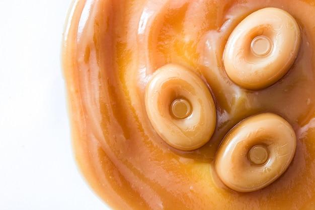 Toffee karamel snoep en karamel saus geïsoleerd op wit copyspace