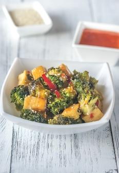 Tofu en broccoli roerbakken met sauzen close-up
