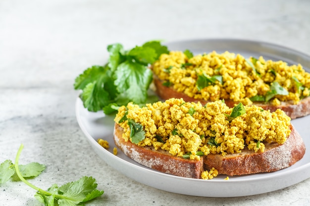 Tofu gooit sandwich op een grijze plaat door elkaar. veganistisch eten concept.