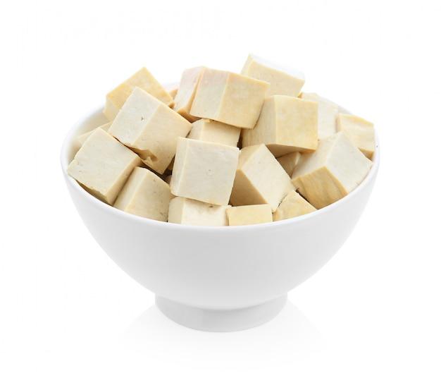 Tofu in een kom die op witte oppervlakte wordt geïsoleerd