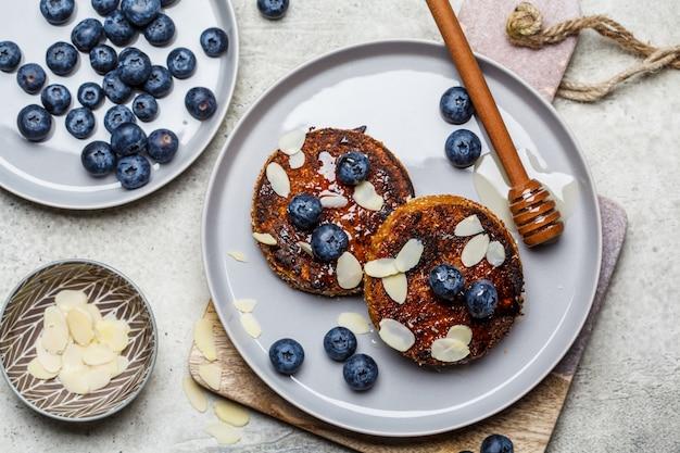 Tofu pannenkoeken met bosbessen en honing op grijze plaat, bovenaanzicht. gezond veganistisch voedselconcept.