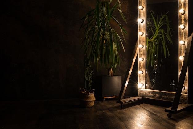 Toilet spiegel staat op een houten vloer met gloeilampen voor verlichting