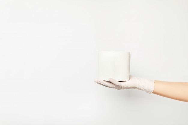 Toiletpapier dat op de hand van een vrouw ligt die een handschoen draagt.