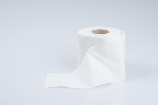 Toiletpapierbroodje op witte muur wordt geïsoleerd die