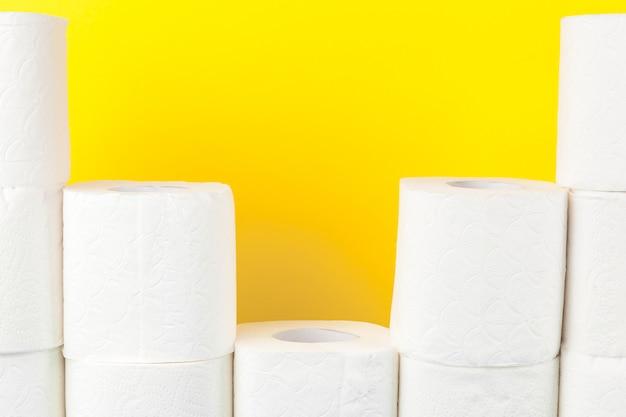 Toiletpapierstapels op helder geel