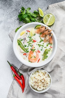 Tom kha gai. pittige romige kokossoep met kip en garnalen. thais eten. grijs oppervlak. bovenaanzicht.
