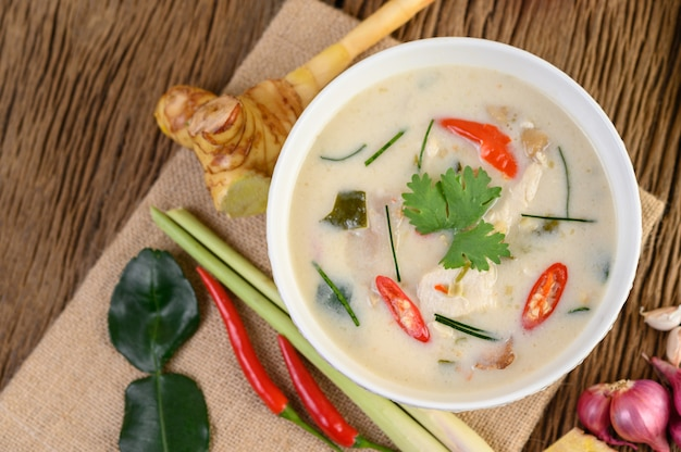 Tom kha kai in een kom met kaffir limoenblaadjes, citroengras, rode ui, laos en chilipeper.