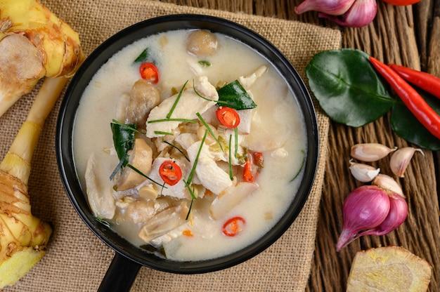 Tom kha kai in een pan bakken met kaffir limoenblaadjes, citroengras, rode ui, laos en chilipeper.