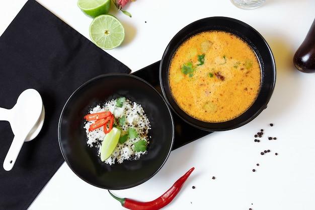 Tom kha. pittige pittige aziatische soep met aubergine, kip, champignons, citroengras, geserveerd met rijst en koriander