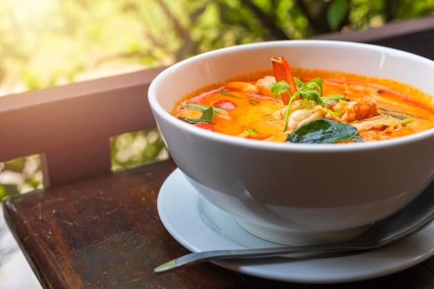 Tom yam kung pittige thaise soep met garnalen in witte kom op houten tafel.