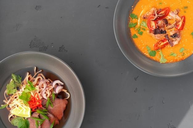 Tom yam-soep en ramen-soep in kommen op grijs bovenaanzicht