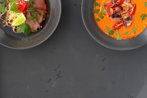 Tom yam-soep en ramen-soep in kommen op grijze hoogste mening als achtergrond