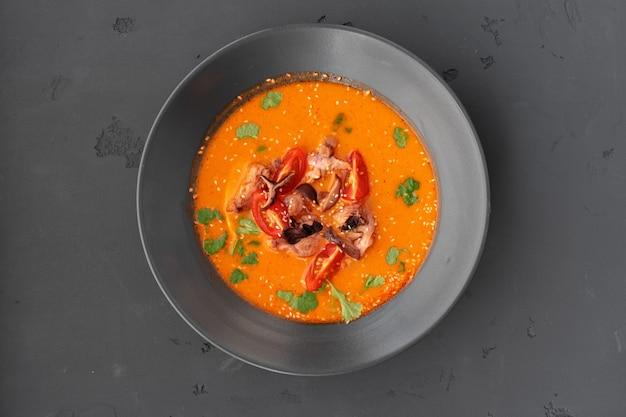 Tom yam thaise soep in zwarte kom die op grijs wordt gediend