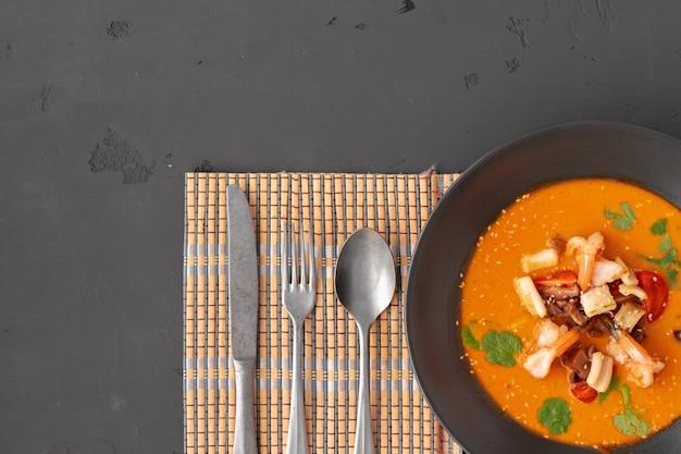 Tom yam thaise soep in zwarte kom geserveerd op een grijze achtergrond bovenaanzicht