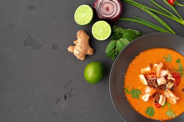 Tom yam thaise soep in zwarte kom geserveerd op een grijze achtergrond