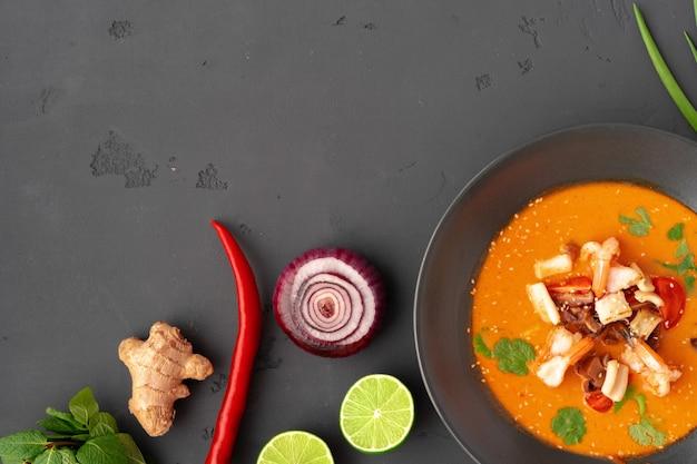 Tom yam thaise soep in zwarte kom geserveerd op een grijze ondergrond