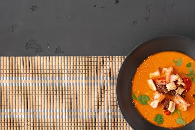 Tom yam thaise soep in zwarte kom geserveerd op grijs bovenaanzicht