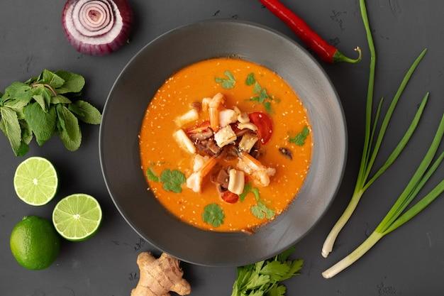 Tom yam thaise soep in zwarte kom geserveerd op grijs