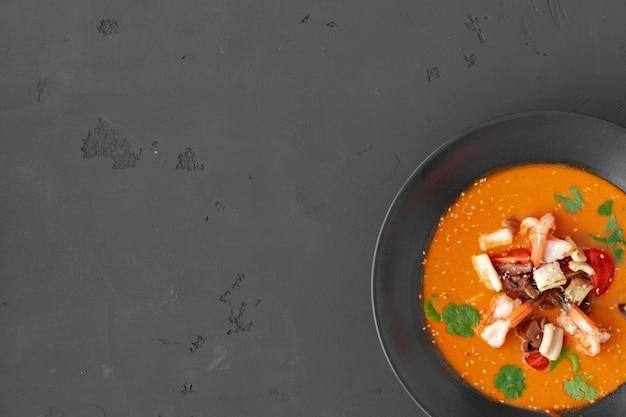 Tom yam thaise soep in zwarte kom geserveerd op grijze tafel bovenaanzicht