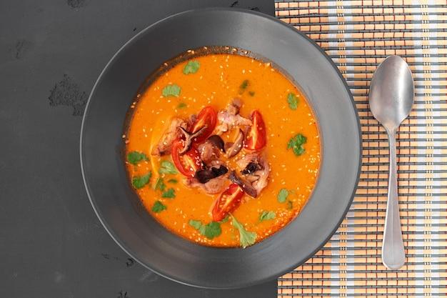 Tom yam thaise soep in zwarte kom geserveerd op grijze tafel