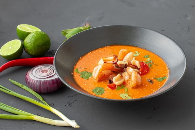 Tom yam thaise soep in zwarte kom op grijze tafel close-up