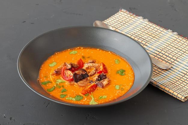 Tom yam thaise soep in zwarte kom op grijze tafel Premium Foto