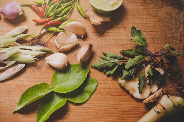Tom yum-kruiden die op een bruine houten snijplank worden geplaatst en een donkerbruin hout hebben.