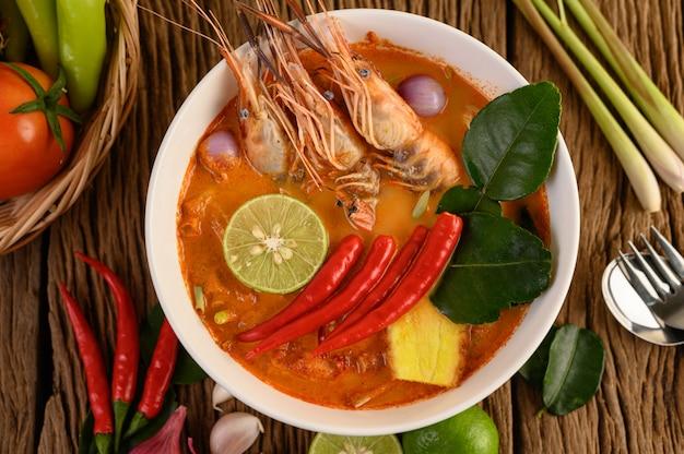 Tom yum kung thaise hete pittige soep garnalen met citroengras, citroen, laos en chili op houten tafel, thailand voedsel