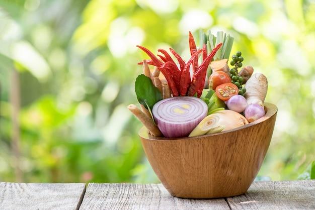 Tom yum of groente en kruiden eten antiviraal en immuun voor het lichaam zoals tomaat, chili, citroengras, limoen, laos, gember, sjalot, paprika, ui, kaempfer en kurkuma op de natuur.