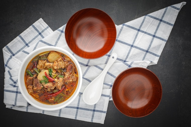 Tom yum, thais eten, hete, pittige en zure gestoofde rundvleessoep in kom met witte keramische lepel, lege houten kommen en tafelservet op donkergrijze tafel