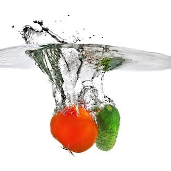 Tomaat en komkommer in water gevallen op wit wordt geïsoleerd
