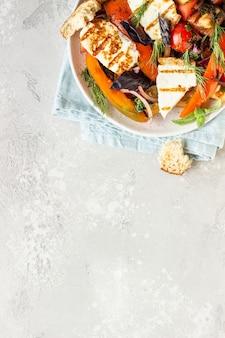 Tomaat, gebakken paprika en uiensalade met gegrilde kaas