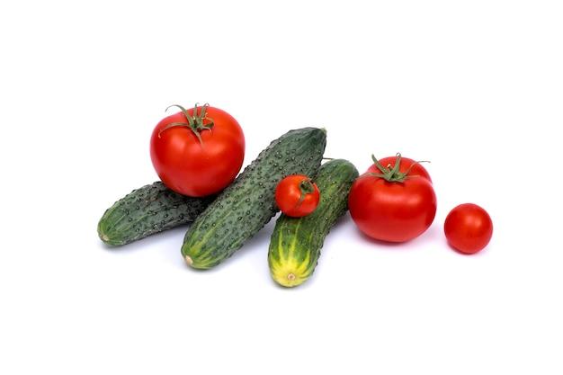 Tomaat met komkommer op witte achtergrond met uitknippad. rijpe groenten geïsoleerd op een witte achtergrond.