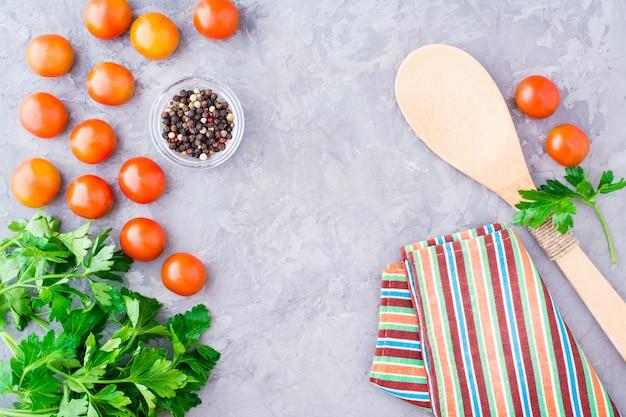 Tomaat, verse kruiden en specerijen op een betonnen tafel, bovenaanzicht