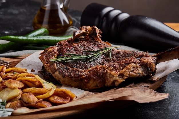 Tomahawk-biefstuk met groenten en een mes op de tafel. gegrild vlees met gegrilde groenten en verse groenten op tafel.