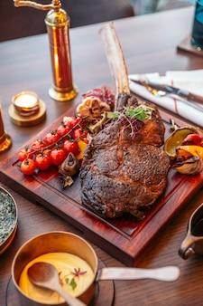 Tomahawk steak met puree aardappel, gebakken spinazie kaas en jus saus. geserveerd met rode wijn.