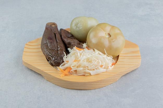 Tomaten, aubergines en zuurkool in een houten bord op het marmeren oppervlak